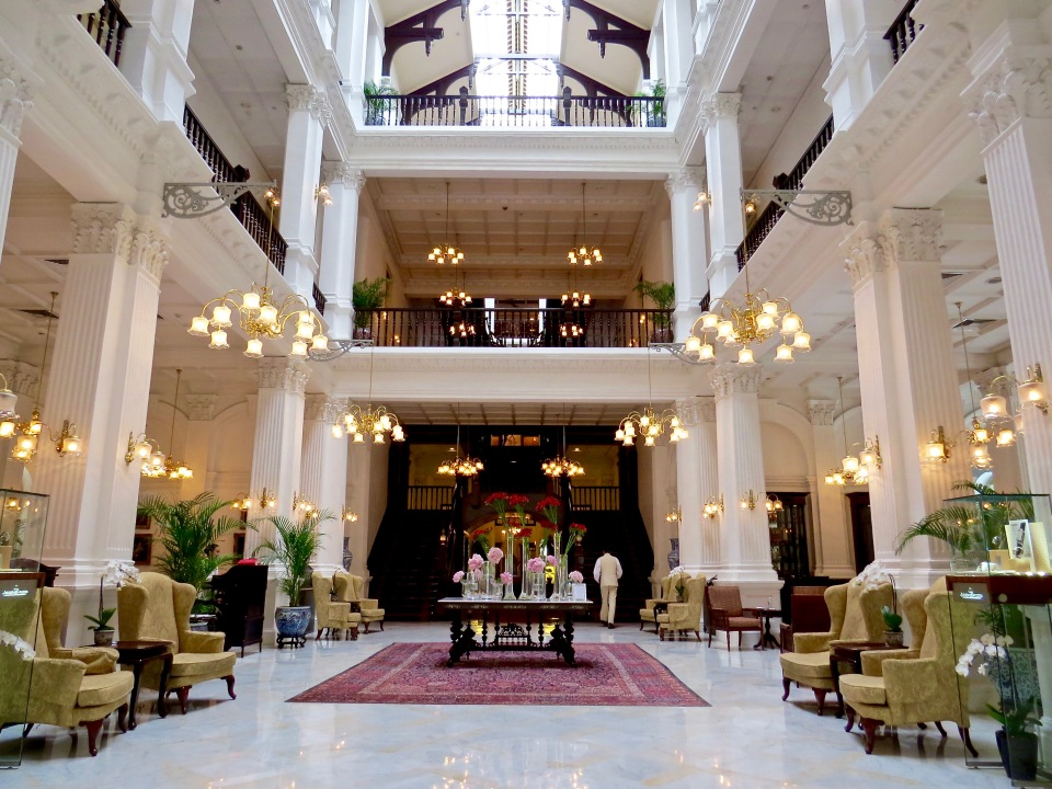 The stunning lobby of the Raffles Singapore Hotel.