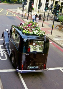 A British Hearse leading a funeral procession.
