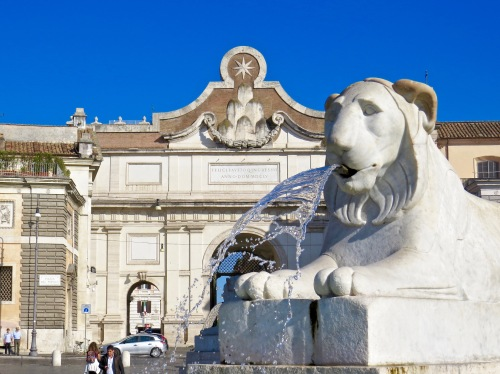 Part of the fountain framed by the Porta del Popolo in the background.
