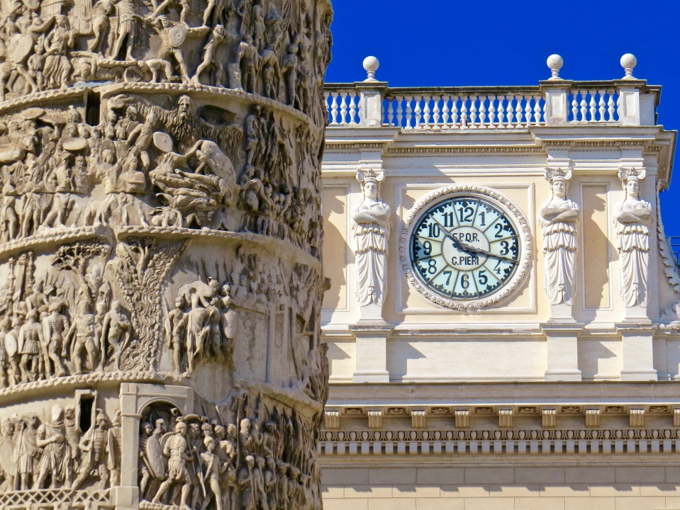 Close up detail of the Column of Marcus Aurelius with the clock of the Palazzo Wedekind in the background.