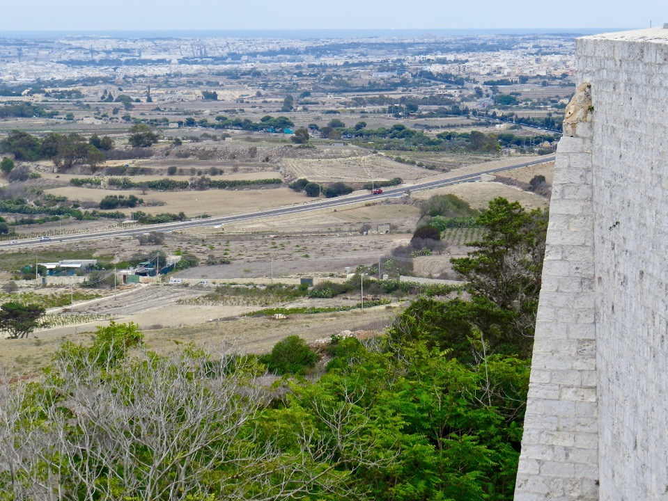 Looking out over Malta, the high wall of Mdina to the right.