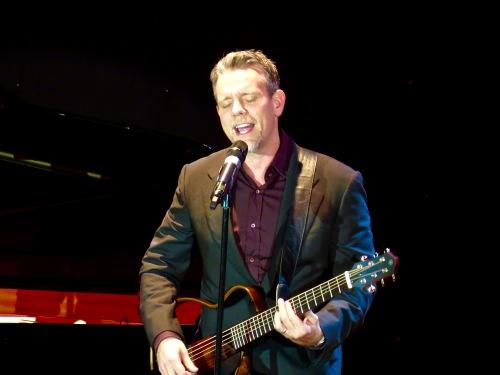 Adam Pascal accompanying himself on guitar.